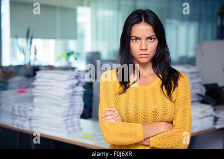 Retrato de enojado empresaria de pie con los brazos plegados en Office Foto de stock