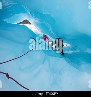 Hembra madura de escalar a través de una cueva de hielo en el glaciar Fox, Isla del Sur, Nueva Zelanda.