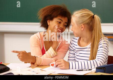 Dos niñas susurran sobre una carta de amor