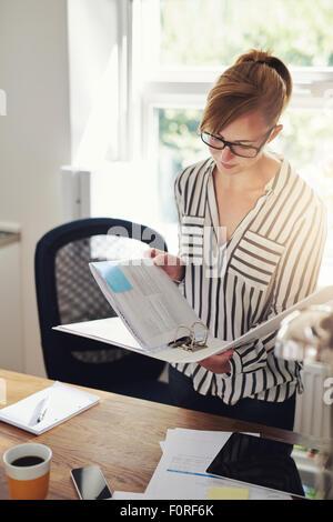 Joven Empresaria en casa trabajando en su oficina permanente en un cuaderno de notas de lectura con una grave expresión
