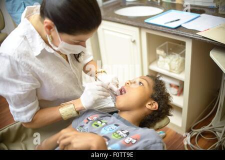 Ortodoncista hembra examinar boy en cirugía dental