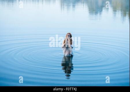 Mujer joven de pie en el lago ripples orando con los ojos cerrados