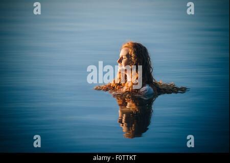 Cabeza y hombros de la mujer joven con largo pelo rojo en el lago con los ojos cerrados