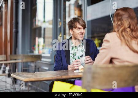 Vista sobre el hombro de la pareja conversando en la cafetería, Londres, Reino Unido.