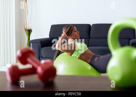 Adulto Joven afroamericana en ropa deportiva en casa, haciendo gimnasia doméstica y entrenamiento abdominales en pelota suiza en l