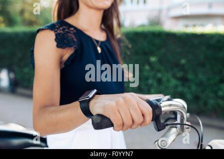 Mujer andar en bicicleta con un smartwatch. Mujeres vistiendo smart watch al ciclismo.