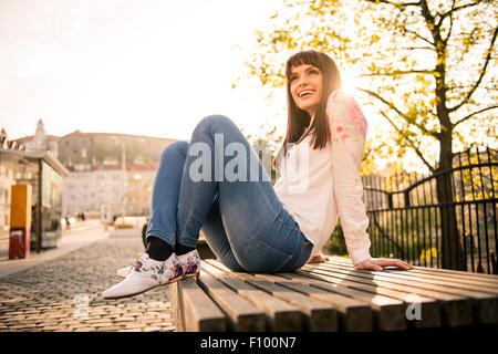 Mujer joven sentado en un banco en la calle y disfrutar de la vida con sun en segundo plano. Foto de stock