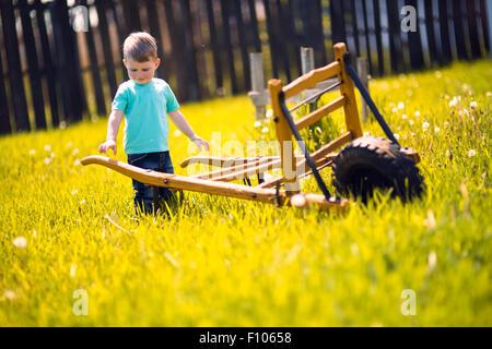 Chico trabajando en los campos y empujando una carretilla de mano