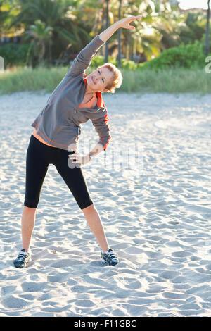 Mujer caucásica estiramiento en la playa