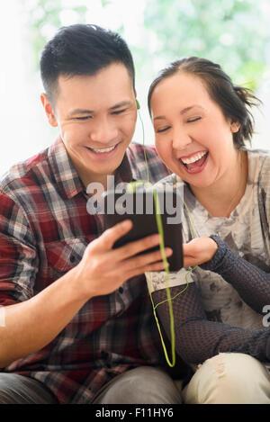 Pareja de risa viendo la tableta digital en el sofá