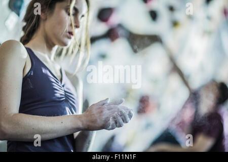 Atleta entizamiento sus manos en la pared de roca en el gimnasio Foto de stock
