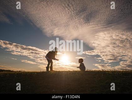 Silueta de una chica con un bebé aprendiendo a caminar Foto de stock