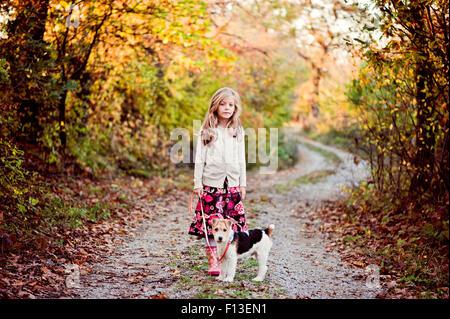 Chica caminar su perro Fox Terrier en el bosque