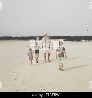 Vista trasera de un hombre con tres hijos, caminar en la playa