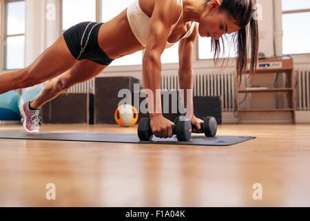 Joven fuerte empuje ups haciendo ejercicio con pesas en la estera del yoga. Modelo de Fitness haciendo un intenso entrenamiento en el gimnasio.