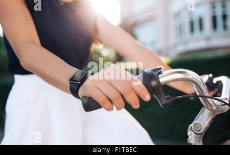Mujer andar en bicicleta con un smartwatch. Mujeres vistiendo smart watch al ciclismo. Reloj inteligente concepto.