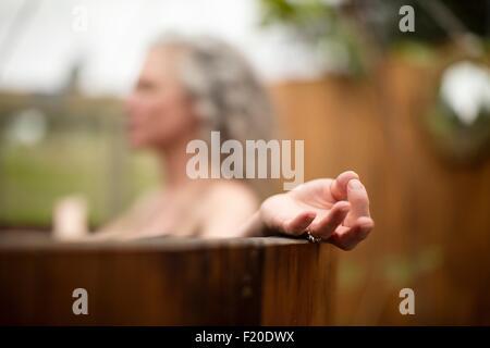 Mujer madura, meditando en el ofuro en eco retreat