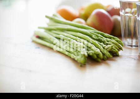 Espárragos, frutas, vaso para beber en la mesa de comedor