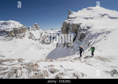 Esquí alpinistas escalada en montaña nevada, Val Gardena, Trentino-Alto Adige, Italia Foto de stock