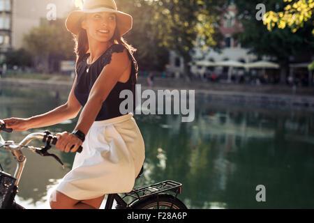 Retrato de mujer joven feliz en bicicleta por un estanque apartar la mirada sonriendo. Mujer con sombrero en un día de verano montando su bicicleta.