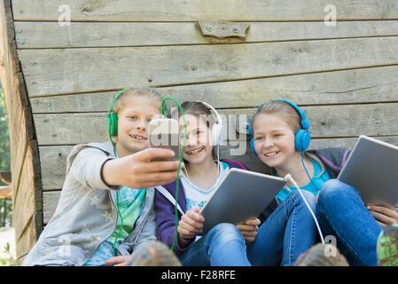 Tres amigos sentado en el patio de recreo y escuchando música, Munich, Baviera, Alemania