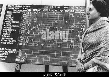 El Primer Ministro de la India, Indira Gandhi, junto a un tablón de anuncios mostrando los primeros actas electorales. Foto de stock