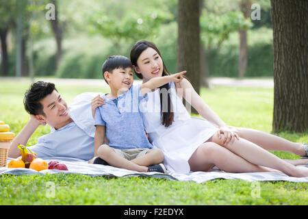 Feliz familia joven tener un picnic en la hierba
