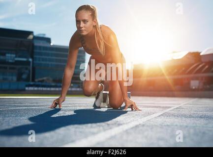 Montar y seguros de mujer en posición inicial listo para ejecutar. Atleta Femenina a punto de empezar un sprint mirando a otro lado. Sunl brillante