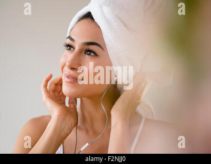 Mujer con pelo en toalla escuchar auriculares Foto de stock