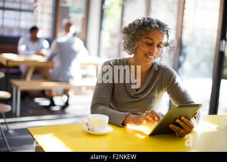 Mujer de edad utilizando digital comprimido en cafe