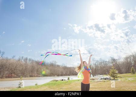 Caucasian niña jugando con cintas en park