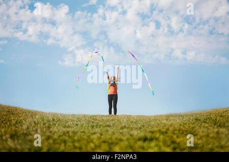 Caucasian niña jugando con cintas en la colina