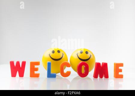 Cartel de bienvenida con dos smileys sobre fondo blanco.