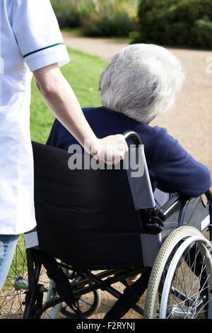 Cerca de cuidador empujando mujer mayor en silla de ruedas Foto de stock