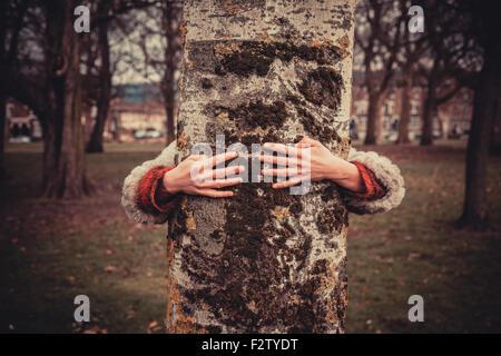 Mujer joven está en el parque en un día de invierno y está abrazando un árbol