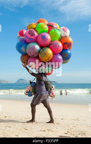 Río de Janeiro, Brasil - 20 de enero de 2013: Playa proveedor de colorida balones de playa lleva su mercancía a lo largo de la playa de Ipanema.