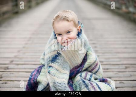 Retrato de un niño envuelto en una manta, sentado sobre un puente de madera