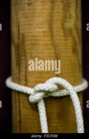 Cuerda atada en el nudo alrededor del poste de madera