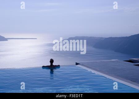Silueta femenina en la piscina infinity en el borde del acantilado mirando hacia el mar azul, Santorini, Grecia, Foto de stock