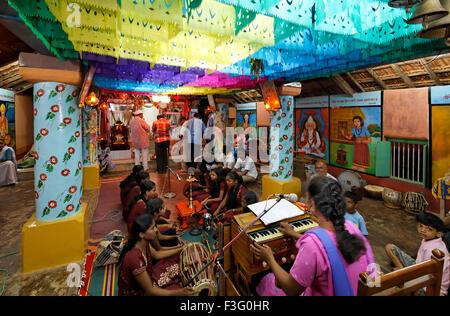 Niñas cantando bhajan tocando instrumentos musicales harmonium tabla en el templo ; India ; asia