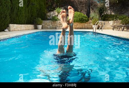 Las piernas y los pies del joven boca abajo en la piscina