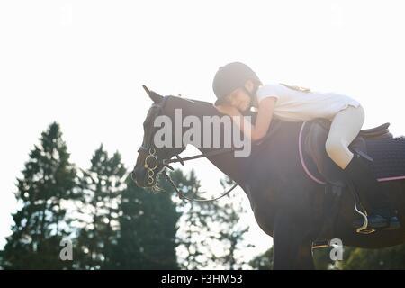 Chica a caballo al inclinarse hacia delante para mascota caballo