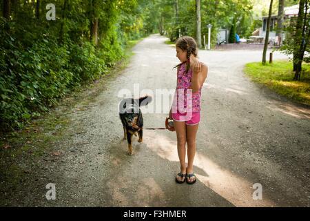 Vista frontal de la chica en el camino de tierra, paseando a un perro, mirando por encima del hombro