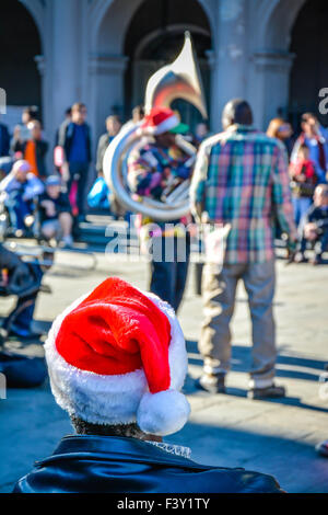Vista trasera del hombre vestido con gorro de Papá Noel para disfrutar de entretenimiento a cargo de músicos de calle, Jackson Square, en el Barrio Francés de Nueva Orleans, LA, Foto de stock