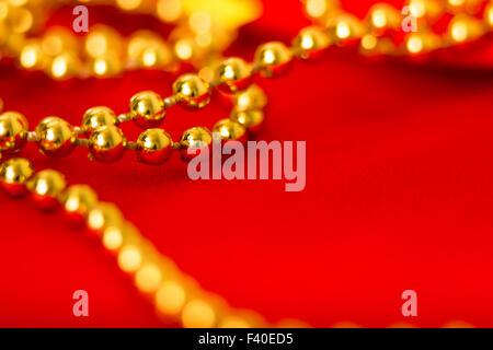 Cordones de oro sobre tela roja de macro.