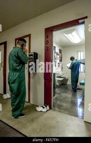 Los adolescentes hispanos uniformados naranja reclusos de una prisión de menores, CA, utilice un teléfono de pago y se lee en su celda. Nota falta de bares. Foto de stock