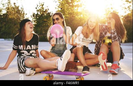 Amigos divertirse en un parque con skateboards y gafas de sol