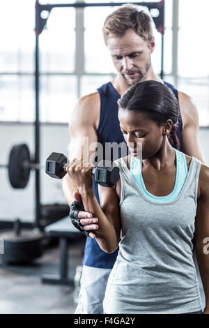 Entrenador masculino ayudar a mujer con pesa