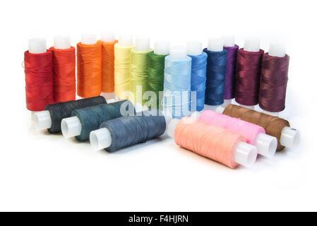 Multicolores hilos para coser en bobinas aisladas sobre fondo blanco.