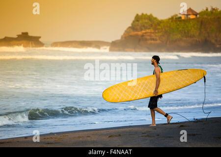 Indonesia, Bali, surfer caminar en la playa Foto de stock